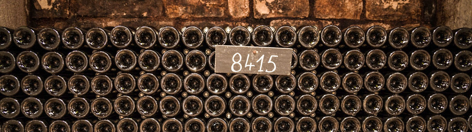 A picture of a wine cellar housing multiple rows of wine bottles