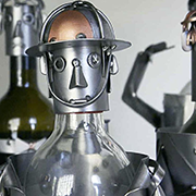 A tin-man wine-bottle topper invites you to refer a friend to receive $50 off your next purchase.