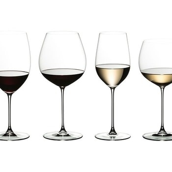 Four wine glasses stand side-by-side. On the left are two glasses filled with red wine, one in a skinny goblet and one in a large goblet. On the right are two glasses filled with white wine, one in a skinny goblet and one in a large goblet.