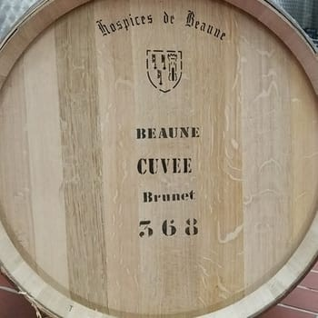 A close-up of the side of a wine barrel from historical wine auction Hospices de Beaune, which Elden Selections participates in every year. The wine barrel is printed with the words, Hospices de Beaune, Beaune Cuvee Brunet 368.